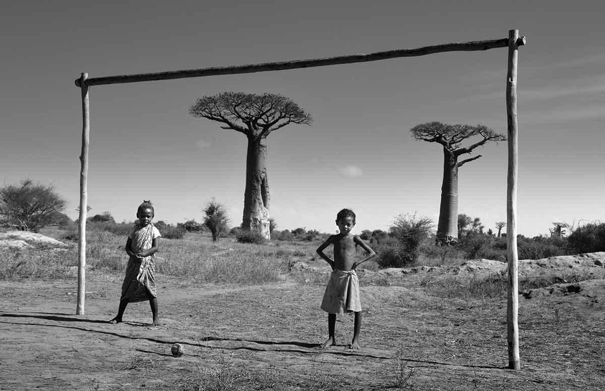 Deux enfant jouant au football devant l'avenue des baobabs à Madagascar